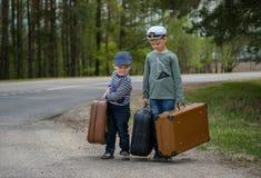 Dwa chłopiec iść na drodze z dużymi walizkami Obrazy Stock