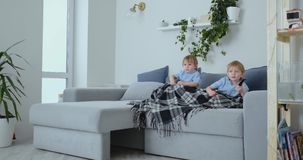 Dwa chłopiec, 4 i 2 lat, ogląda TV obsiadanie na leżance Podniecający program telewizyjny Widok kreskówki Dzieci oglądają zbiory wideo