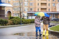 Dwa chłopiec, kucnięcie na kałuży z małymi parasolami, zdjęcia stock