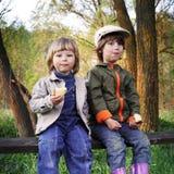 Dwa chłopiec na lasowej ławce Zdjęcia Stock