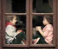 Dwa chłopiec na nadokiennym, śmiający się herbaty i pijący Fotografia Stock