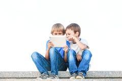 Dwa chłopiec patrzeje pastylka komputer osobistego Dzieciństwo, edukacja, uczenie, technologia, czasu wolnego pojęcie Zdjęcia Stock