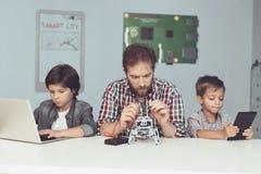 Dwa chłopiec pracują na pastylce i laptopie, między one buduje i siedzi robot mężczyzna Obrazy Royalty Free