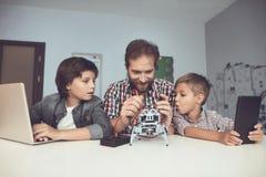 Dwa chłopiec pracują na pastylce i laptopie, między one buduje i siedzi robot mężczyzna Zdjęcie Royalty Free