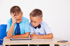 Dwa chłopiec siedzą przy przyglądającą pastylką i biurkiem obraz stock