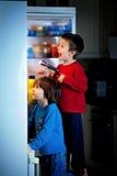 Dwa chłopiec, skrycie je cukierki od fridge przy nocą Fotografia Royalty Free