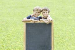 Dwa chłopiec stoi przy blackboard Odbitkowa przestrzeń dla teksta Zdjęcia Royalty Free
