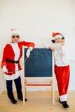 Dwa chłopiec udaje jest Zły Santa blisko czerni deski Zdjęcie Stock