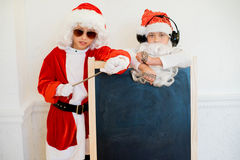 Dwa chłopiec udaje jest Zły Santa blisko czerni deski Obrazy Royalty Free