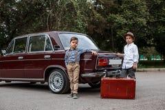 Dwa chłopiec w roczników ubraniach stoją bezczynnie retro samochód obrazy stock