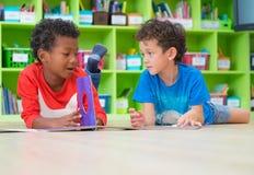 Dwa ch?opiec dzieciak k?a?? puszek na pod?oga i czytelniczej bajki ksi??ce w preschool bibliotece, dzieciniec edukaci szkolnej po zdjęcia royalty free