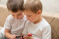 Dwa chłopiec trzyma smartphone obraz royalty free