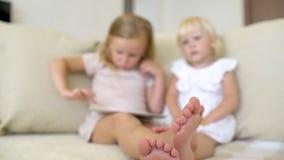 Dwa childs ogląda ang używać pastylkę w domu Dzieci używa nowożytnego laplop, pastylka na kanapie Małe dziewczynki bawić się dale zbiory wideo