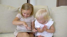 Dwa childs ogląda ang używać pastylkę w domu Dzieci używa nowożytnego laplop, pastylka na kanapie Małe dziewczynki bawić się dale zbiory