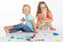 Dwa childs rysują farbami na białym papierze Obrazy Royalty Free