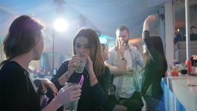 Dwa chmielnej dziewczyny rozmowy przy klubem z szkłami za zakazują kontuar na tle światła zbiory wideo