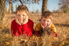 Dwa chłopiec kłama na jesień parku Fotografia Stock
