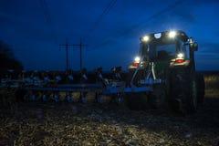 Dwa ciągnik orze ziemię póżno przy nocą z reflektorami dalej obraz stock