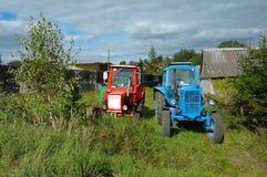 Dwa ciągnika w wiosce blisko drewnianego domu, czerwieni i błękita trac, Fotografia Royalty Free