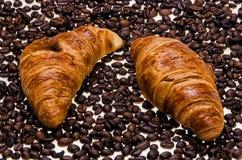 Dwa croisants z kawowymi fasolami Obrazy Stock