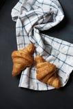 Dwa croissant świeży lying on the beach na blackboard Także, tam jest przekręcający bieliźniany ręcznik Obrazy Stock