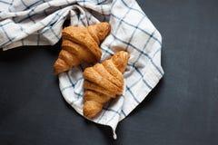 Dwa croissant yummy lying on the beach na czarnym stole Także, tam jest przekręcający bieliźniany ręcznik Fotografia Royalty Free