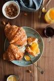 Dwa croissants z crispy skorupy kłamstwem na talerzu na drewnianym stole obok herbaty, migdałów, rocznik łyżki i morelowego dżemu Zdjęcie Royalty Free