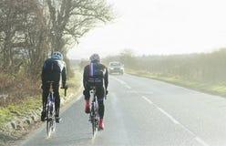 Dwa cyklisty Ściga się Na Ruchliwie wiejskiej drodze Jeziorny Gromadzki Anglia 1st 2017 Grudzień Fotografia Stock