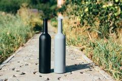 Dwa czarnej i szarość butelki na drodze od płytek wioska, wiejski alkoholizm, pijaństwo alkoholiczna choroba wino naturalny zdjęcia royalty free