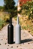 Dwa czarnej i szarość butelki na drodze od płytek wioska, wiejski alkoholizm, pijaństwo alkoholiczna choroba wino naturalny fotografia stock
