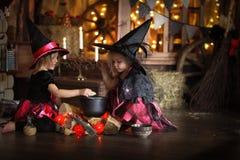 Dwa czarownic mały Halloweenowy czytać czaruje nad garnka childh Obrazy Royalty Free