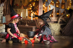 Dwa czarownic mały Halloweenowy czytać czaruje nad garnka childh Zdjęcie Stock