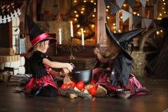 Dwa czarownic mały Halloweenowy czytać czaruje nad garnka childh Zdjęcia Royalty Free