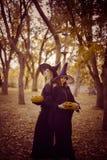 Dwa czarownicy stoi pomarańczowej bani i trzyma Obrazy Royalty Free