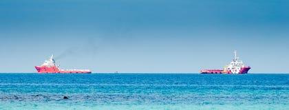 Dwa czerwieni ładunku statek na głębokim błękitnym morzu Obraz Stock
