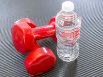 Dwa czerwieni dumbbell ciężaru obok jasnej butelki wodny lying on the beach dalej Fotografia Stock