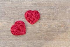 Dwa czerwieni szydełkowego serca na drewnianym tle dla walentynka dnia zdjęcie royalty free