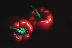 Dwa czerwonego dzwonkowego pieprzu na ciemnym tle Obraz Royalty Free