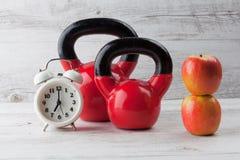 Dwa czerwonego kettlebells z jabłkami i zegarem, Zdjęcia Royalty Free