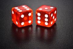 Dwa czerwonego luminescencyjnego kasynowego kostka do gry na czarnym odbija tle obraz royalty free