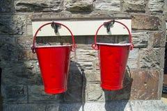 Dwa czerwonego pożarniczego wiadra przeciw kamiennej ściany tłu fotografia royalty free