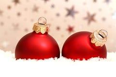 Dwa czerwonej Bożenarodzeniowej piłki w śniegu Zdjęcia Stock