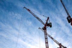 Dwa czerwonej przemysłowej budowy basztowego żurawia przeciw niebieskiemu niebu w tle - pojęcie nieruchomości pracy biznesowa ere fotografia stock