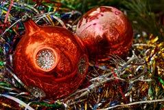 Dwa czerwonej szklanej Bożenarodzeniowej piłki w barwionych ornamentach Zdjęcia Stock