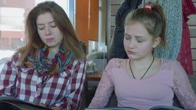 Dwa długowłosej blondynki w cukiernianym spojrzeniu przy menu wtedy one uśmiechają się i zbiory