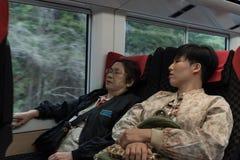 Dwa damy azjatykcia kobieta siedzą w pociągu, jeden sen, jeden spojrzenia throug Obrazy Stock