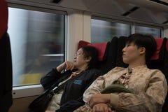 Dwa damy azjatykcia kobieta siedzą w pociągu, jeden sen, jeden spojrzenia throug Obraz Royalty Free