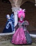 Dwa damy jest ubranym jaskrawy barwione maski i kostiumy przy Wenecja karnawałem błękitne i różowe Obrazy Stock