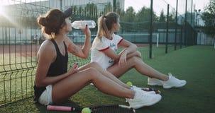Dwa damy przerwa czas przy tenisowego sądu wodą pitną, one są siedzącym puszkiem na sztucznej zielonej trawie przy zbiory