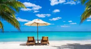 Dwa deckchairs na idyllicznym bielu wyrzucać na brzeg turkusowego morze Obrazy Royalty Free